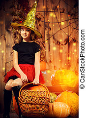 witchcraft - Pretty little girl witch posing with pumpkins...