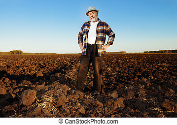 farmer in a field - An elderly farmer standing in a plowed...