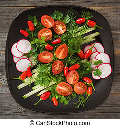 Greens and vegetable salad on a black plate in style rustic...