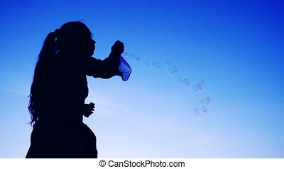 Yong girl blowing the soap bubbles against blue sky, slow motion