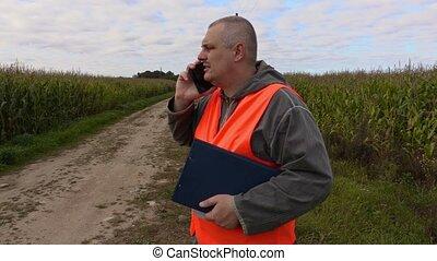 Farmer talking on smart phone at the corn field