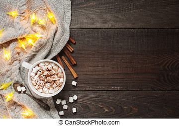 Wooden background with cap of cacao, marshmallow and garland