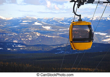 Chairlift - A yellow chairlift over snowy mountains.