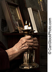 Hands and candles - Old wrinkled hands woman praying with...