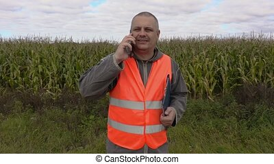 Farmer with folder using smart phone on corn field
