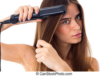 Woman using hair straightener - Young attractive woman with...