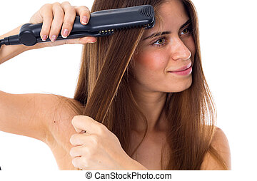 Woman using hair straightener - Young pretty woman with long...