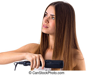 Woman using hair straightener - Young nice woman with long...