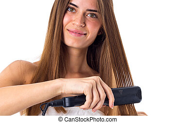 Woman using hair straightener - Smiling young woman with...