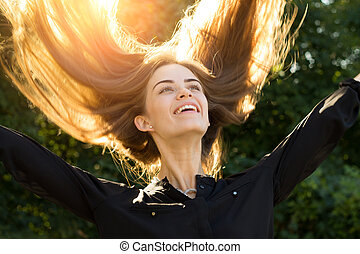 Woman throwing up her long hair - Young happy woman in black...