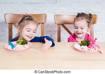 girls play with their food - Two little girl eat delicious...