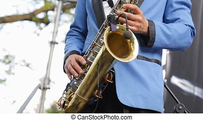 Musician playing saxophone close-up. Wireless microphone...