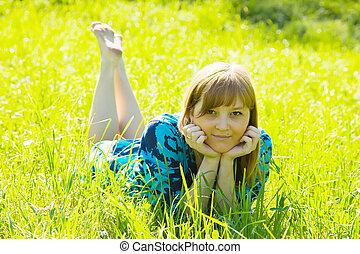 girl is lying on meadow - Pretty teen girl is lying on...