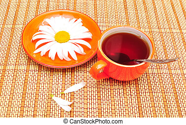 orange cup tea  and camomiles at the background