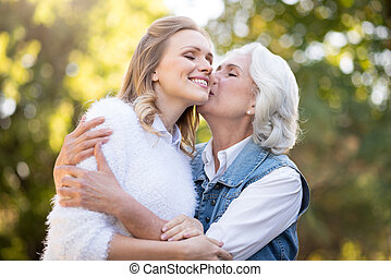 Beautiful gray haired woman kissing her daughter in the...