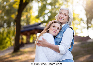 Two friendly beautiful women hugging each other in the park...
