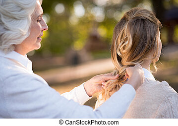 Gray haired women plaiting her daughter hair. - Oh my little...