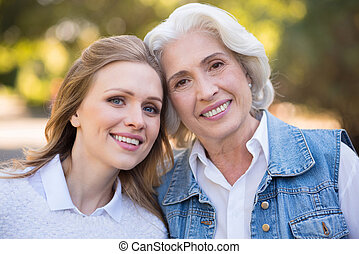 Two beautiful smiling women leaning against each other. - We...
