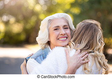 Gray haired woman hugging her daughter - My little adult...