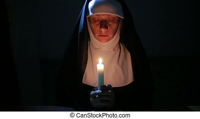 woman nun praying at night burning candles Woman in clothes...
