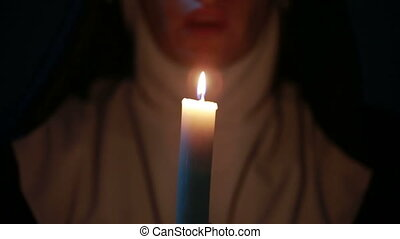 woman nun praying at night. burning candles. Woman in...