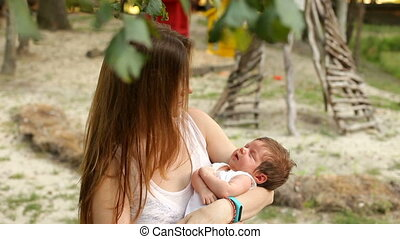 Mother lulling her sleeping baby in the park - Young smiling...