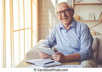 Handsome old man at home - Handsome old man in eyeglasses is...