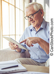 Handsome old man at home - Handsome old man in eyeglasses is...
