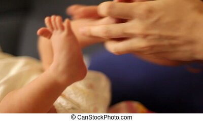 Woman's hands stroking baby's legs - Woman's hands stroking...