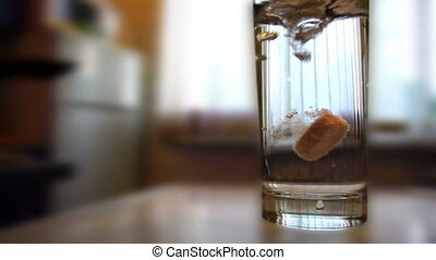 Glass of water with dissolving pill in it standing on the...