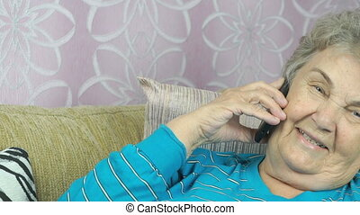 Senior woman with smartphone calling at room - Senior woman...
