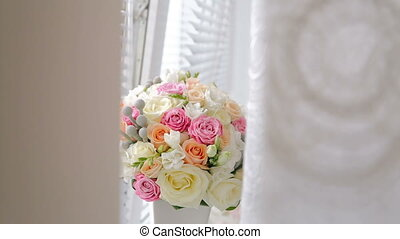 A wedding bouquet on the windowsill in white vase