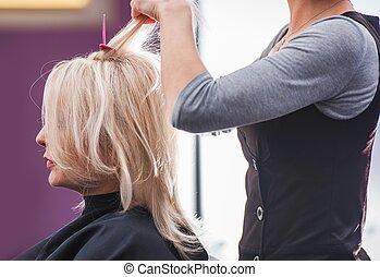Hair Stylist Hair Cut. Caucasian Blond Hair Woman in the...