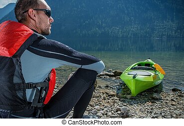 Kayaker and the Lake. Caucasian Kayaker in His 30s Resting...