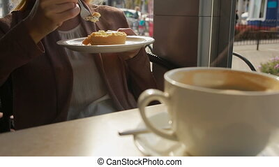 woman eating cake at outdoors cafe. cheese cake closeup -...