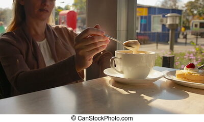 Woman mixing mousse from the coffee and eating it close up...