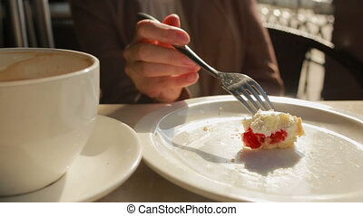 woman eating cake at outdoors cafe cheese cake closeup -...