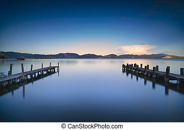 Two Wooden pier or jetty and on a blue lake sunset and sky reflection on water. Versilia Tuscany, Italy