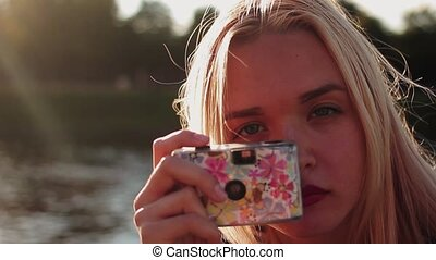 Young woman with a film camera taking pictures and laughs -...
