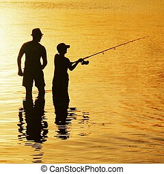 silhouette of father and son fishing at sunset