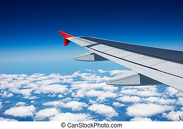 wing of the airplane under the clouds