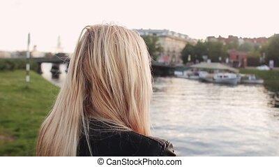 Beautiful young sad girl walking along waterfront at sunset....