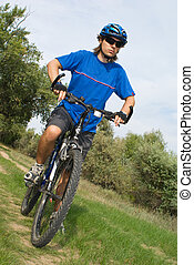 young bicyclist in a blue helmet on nature