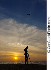 Treasure hunter with Metal detector on sunset the beach a...