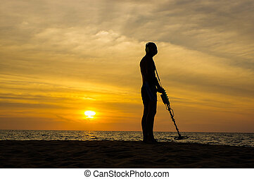 Treasure hunter with Metal detector on sunset the beach - a...