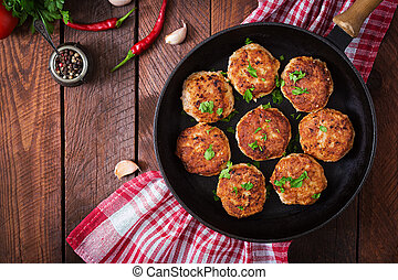 Juicy delicious meat cutlets in pan on a wooden table. Top...