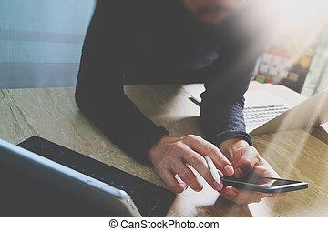 designer using smart phone and keyboard dock digital tablet...