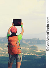 hiker taking photo with digital tablet at seaside mountain...