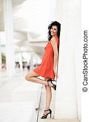 Brunette woman wearing orange short dress in a harbor -...