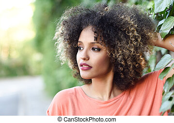 Black woman with afro hairstyle standing in an urban park -...